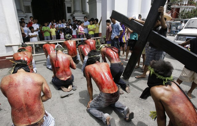 Filipino-flagellants-kneel-in-front-of-the-church-as-they-perform-rites-meant-to-atone-for-sins-at-San-Fernando-city-Pampanga-province-northern-Philippines-on-Maundy-Thursday-April-9-2009.-Many-Philippine-devotees-practice-fla